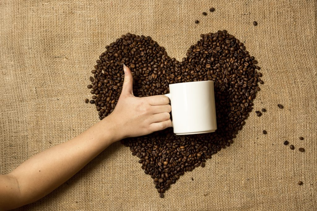 Closeup photo of woman holding mug against heart made of coffee beans